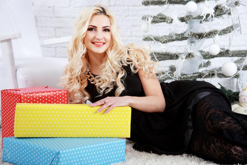 金发女人躺在礼品盒旁边