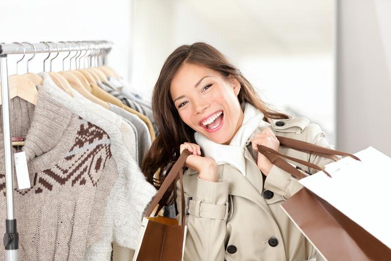 买衣服的女人快乐购物-快乐兴奋的微笑女子-混血白种人/中国亚裔女模特在服装店内穿着风衣拿着购物袋