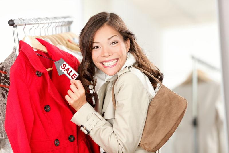 一位购物妇女兴奋地在服装店的服装销售处展示价签-笑容可掬的女人-价格标签上写着减价