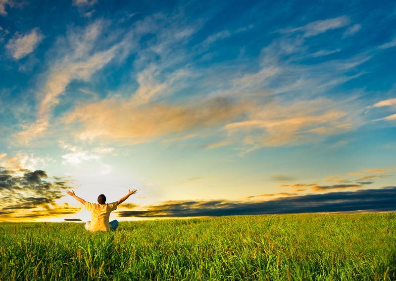日落下坐在田野里的人