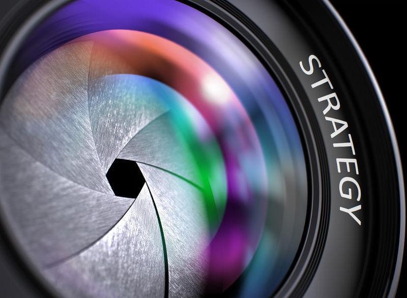 战略概念。特写镜头镜头与美丽的彩色灯光反射。策略写在带快门的摄影镜头上。彩色镜头反射。特写镜头。3D渲染。