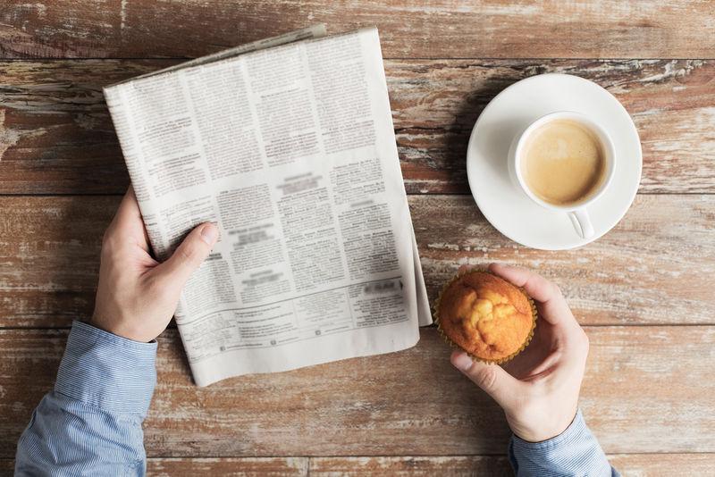 男性手拿报纸和咖啡的特写镜头