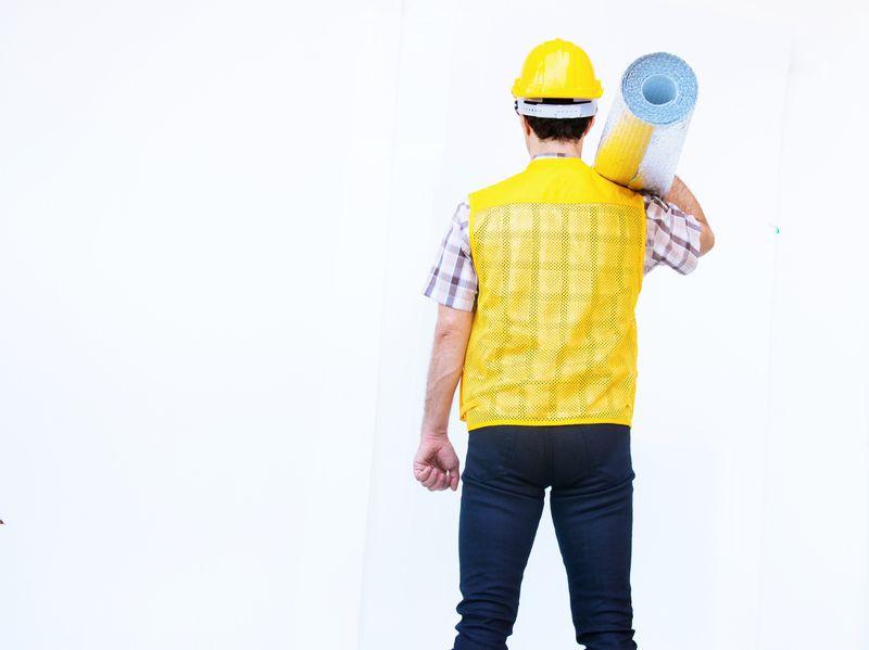 微笑的建筑工人戴着黄色的安全帽,在白色的背景上戴着绝缘材料。