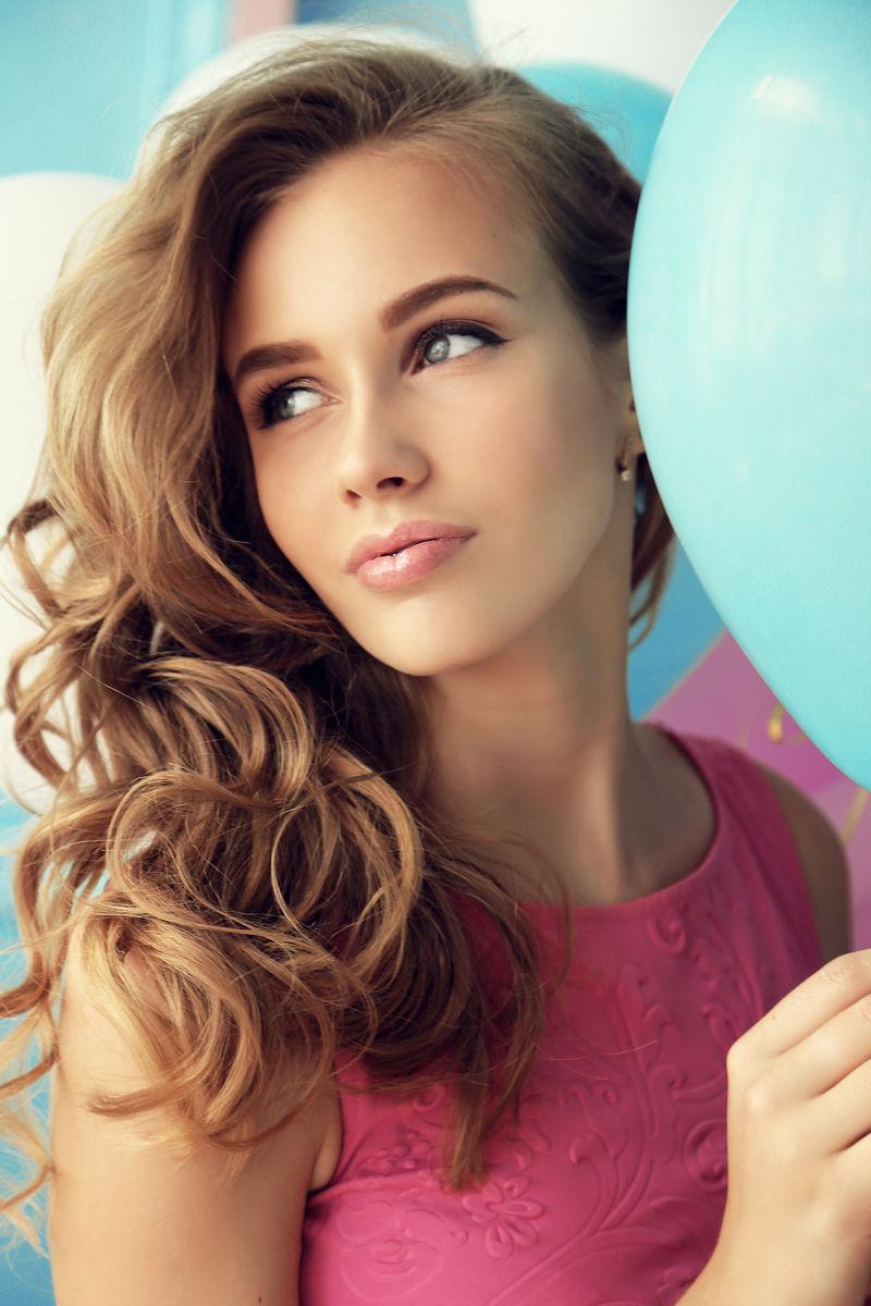 时尚的室内照片,美丽的年轻女孩,深色卷发,温柔妆容,用五颜六色的气球造型。