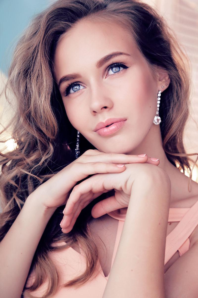 时尚的内部照片,美丽的年轻女孩深色卷发和温柔的妆