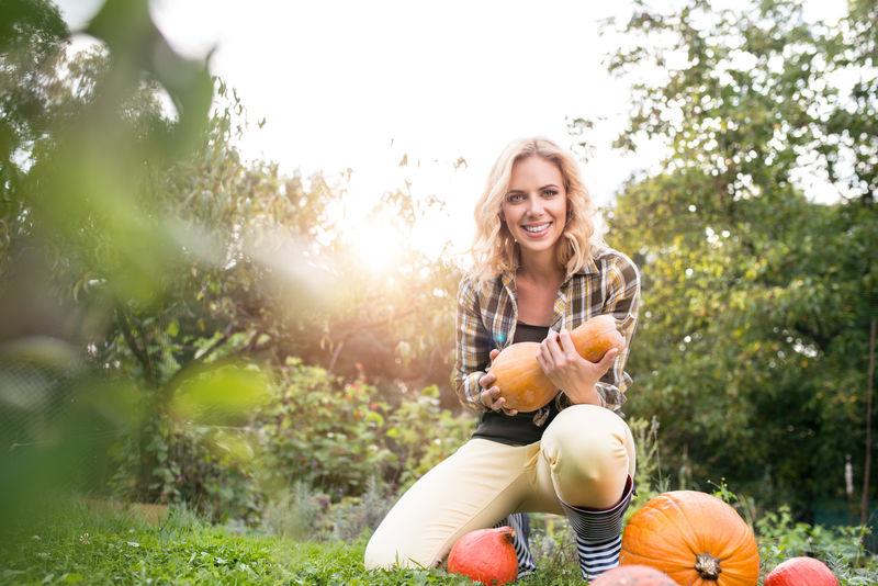 美丽的金发女郎在花园里摘南瓜