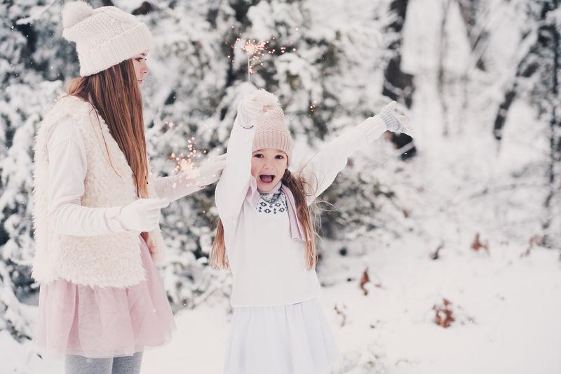 快乐的小女孩在雪天户外玩得开心。玩火花。童年。