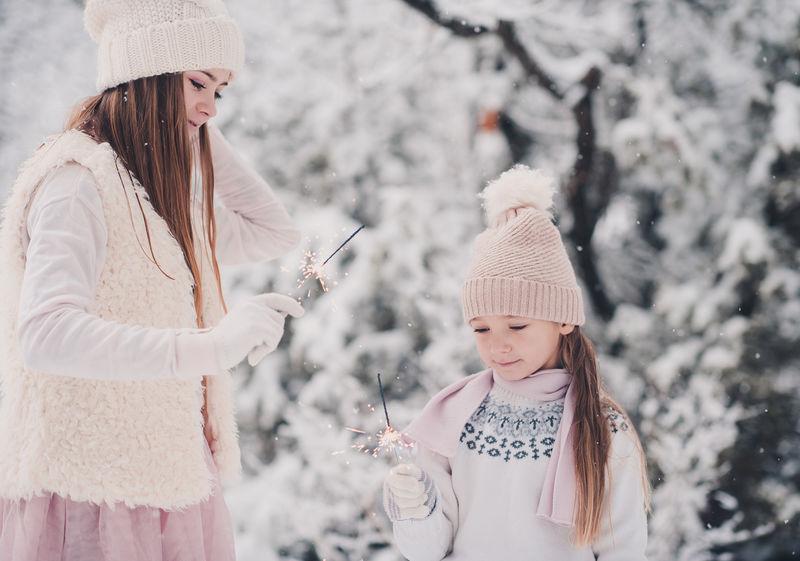 有趣的小女孩在户外的雪地上玩火花。冬季。幸福。