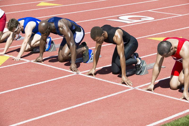 多民族男子田径队在起跑线上等待