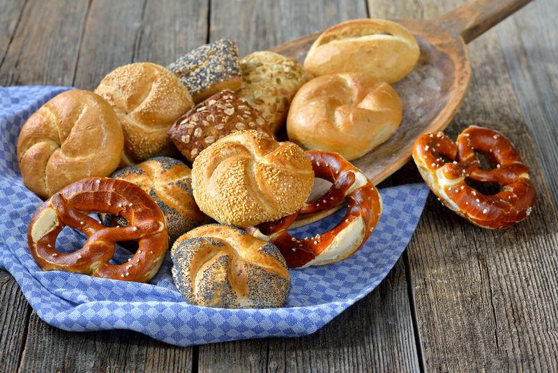 将新鲜的巴伐利亚面包卷和椒盐脆饼放在老式烤盘上烤制