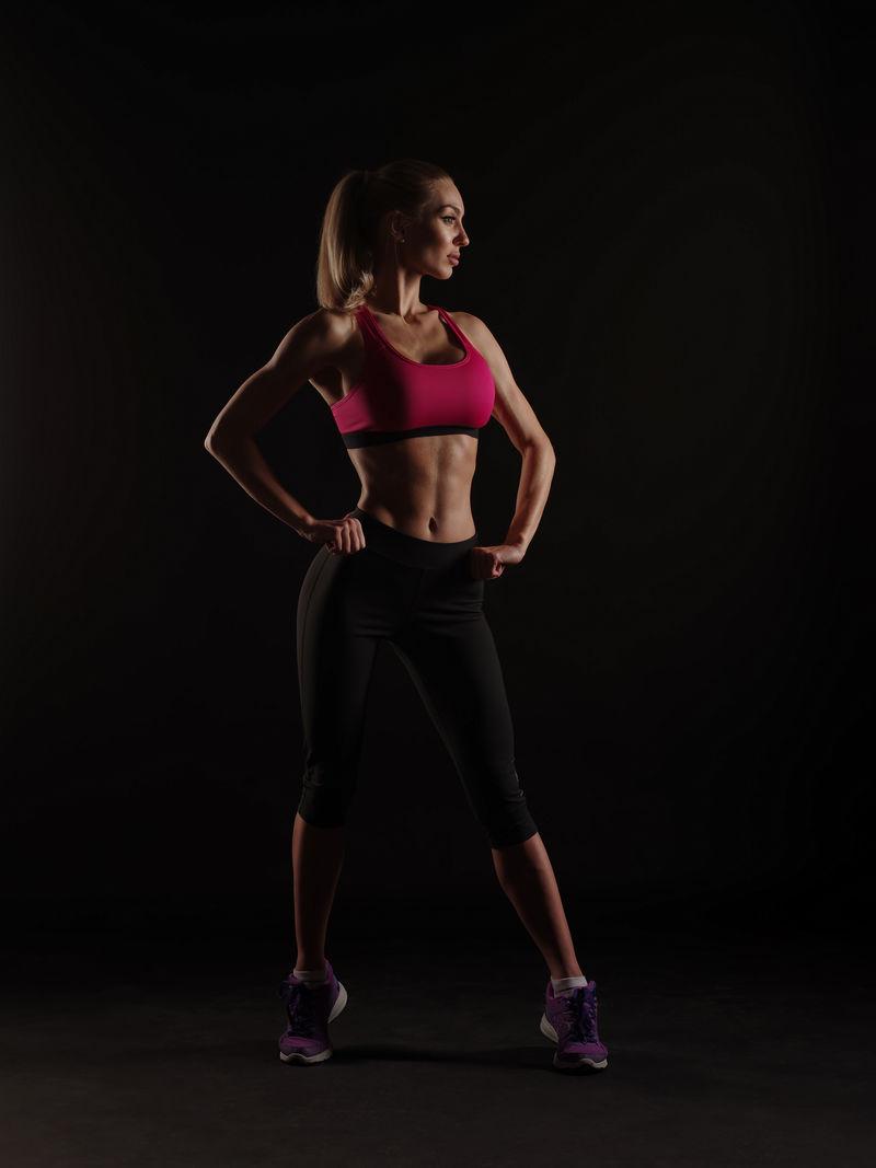 美丽的运动型年轻女性,身材苗条,头发整齐,穿着运动服,在黑色的背景下,节食,健身。