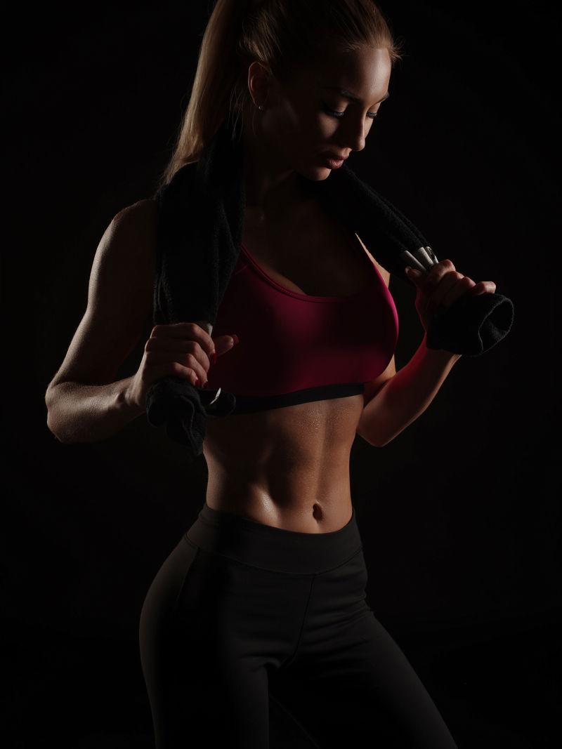 性感强悍的运动型年轻女性,身材苗条,头发整齐,穿着运动服,在摄影棚的深黑色背景下摆姿势,腹部出汗,身体健康