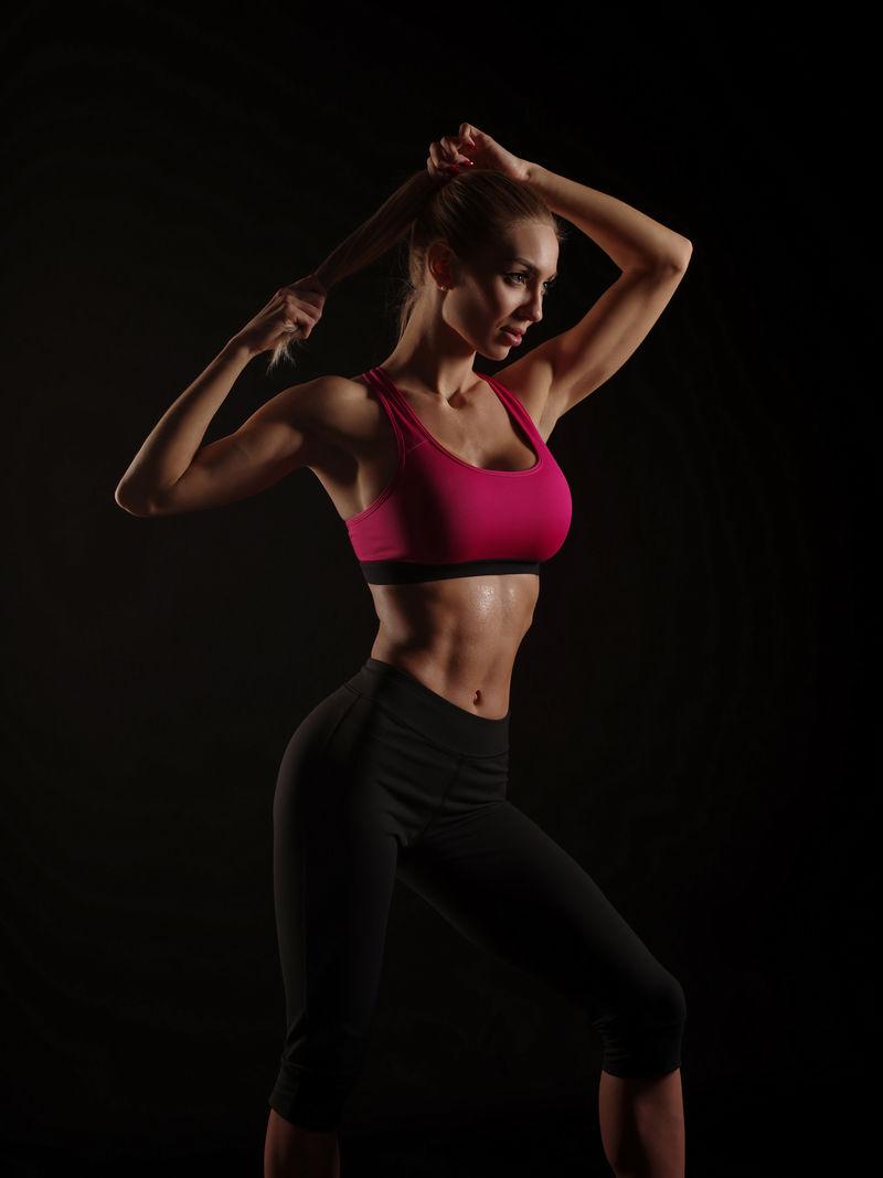 迷人的运动女孩,完美苗条的身材,穿着运动服,在深黑色的背景下用毛巾摆姿势,饮食和健康的生活方式,摄影棚拍摄