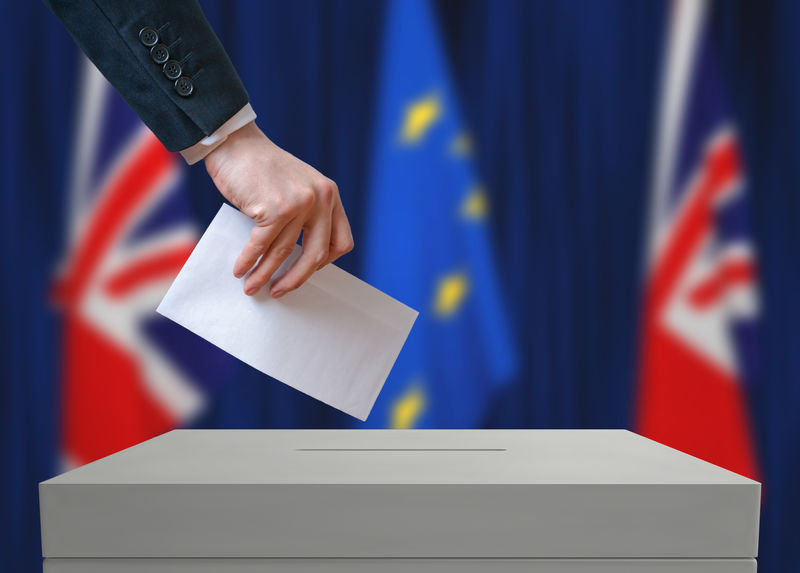 英国的选举或公投。投票者手里拿着信封。背景是英国和欧盟的旗帜。