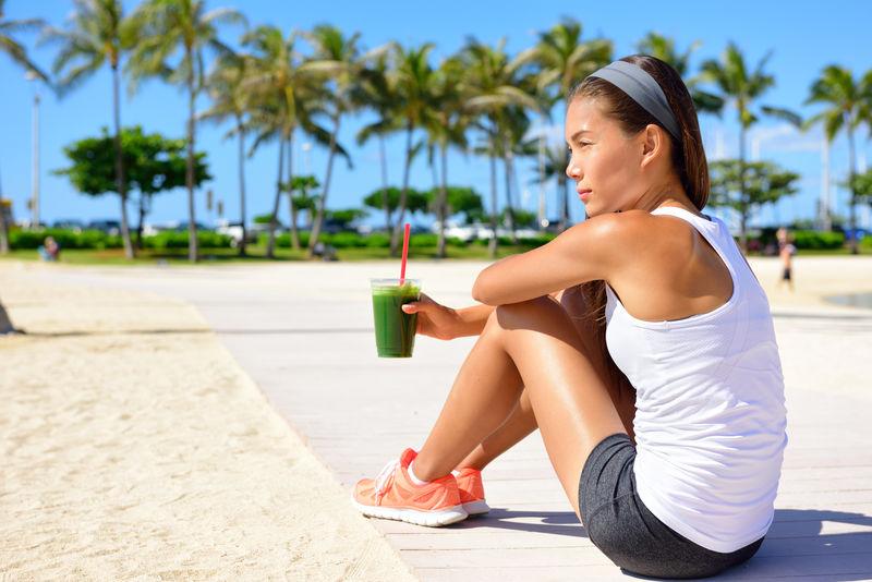 健康女跑步者喝绿色冰沙