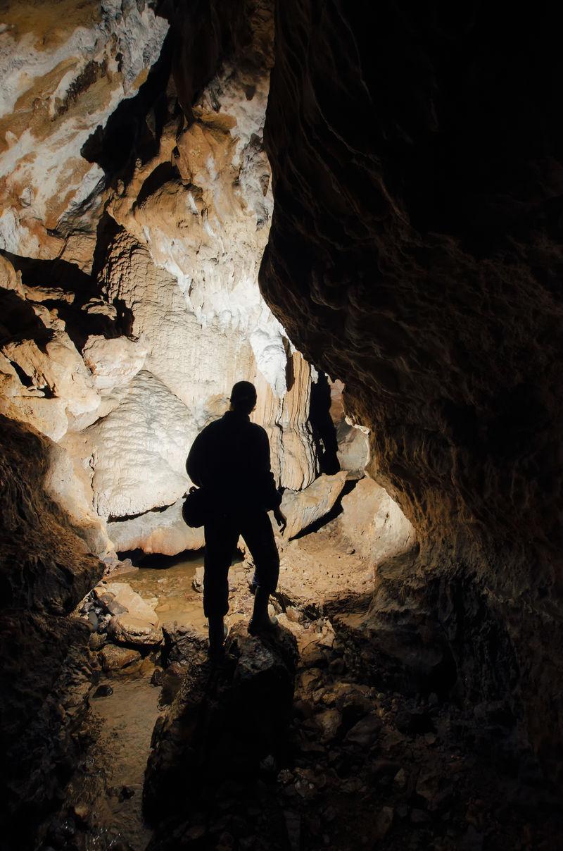 带有探险家轮廓的黑暗洞穴