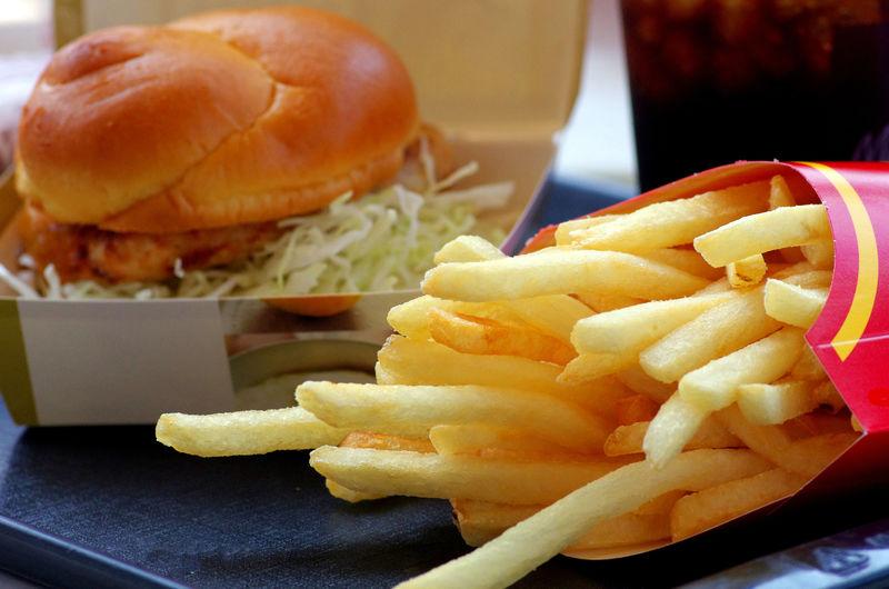 美味的自制芝士汉堡-放在薯条旁边的木盘上-快餐-不健康零食