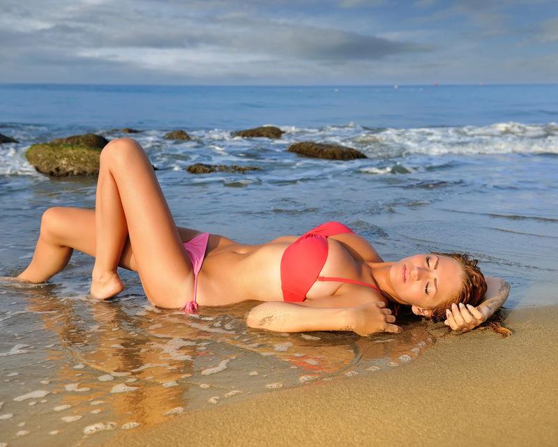 在海滩上放松的年轻性感女人