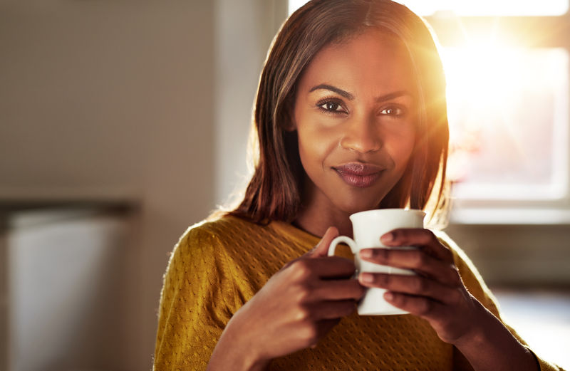 微笑友好的年轻黑人妇女喝咖啡