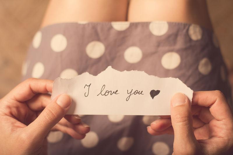 """女人拿着一张纸条,上面写着""""我爱你"""""""
