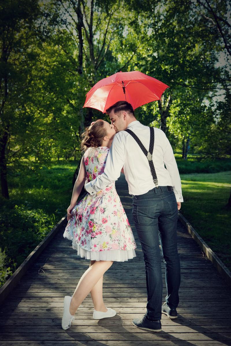 恋爱中的年轻浪漫情侣在雨中调情。红伞