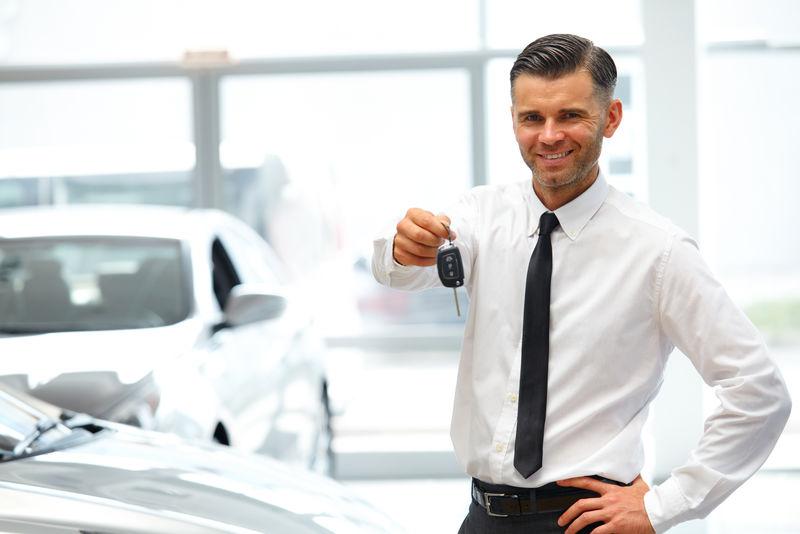 汽车销售员在陈列室给新车钥匙