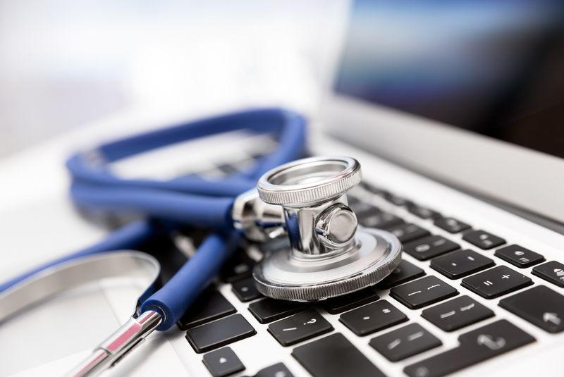 笔记本电脑键盘上的听诊器-医疗或IT安全概念