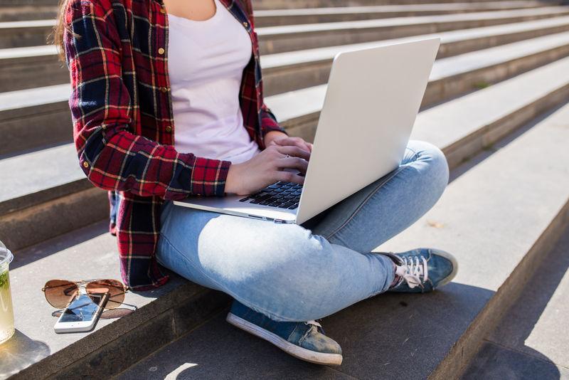 特写快乐的年轻女子坐在城市的楼梯上,在户外使用笔记本电脑