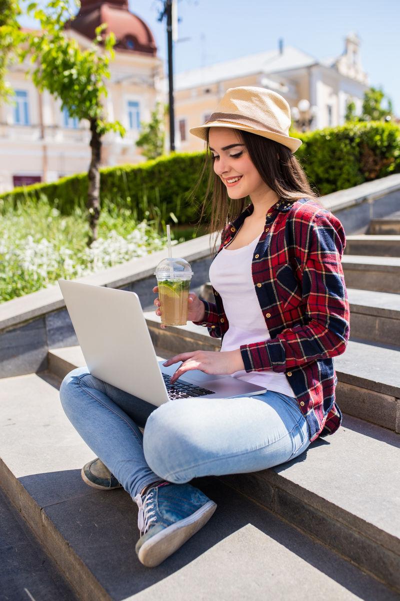 一个快乐的年轻女子坐在城市的楼梯上,在户外使用笔记本电脑