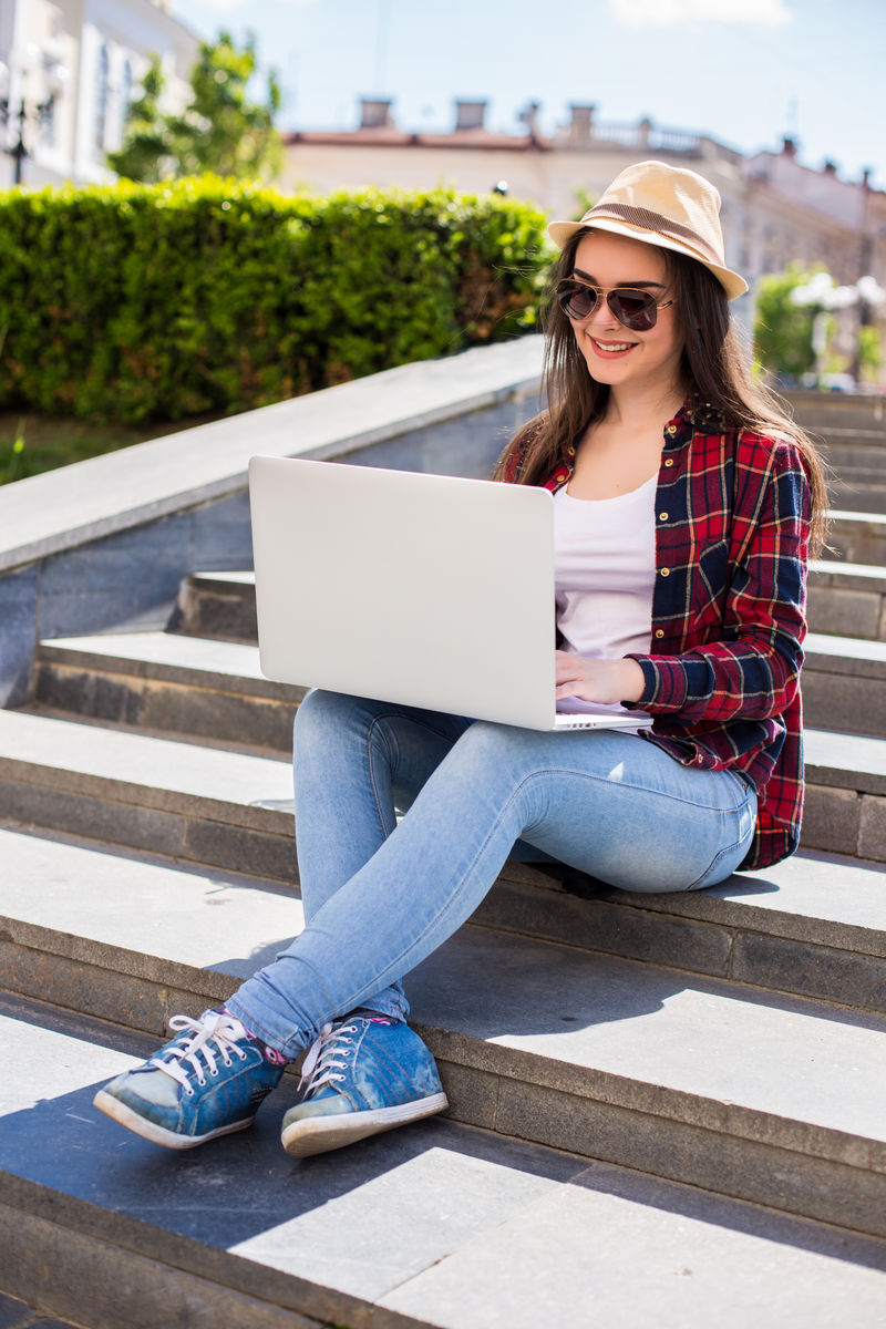 一位戴着太阳镜、坐在城市楼梯上、在户外使用笔记本电脑的快乐年轻女子的画像