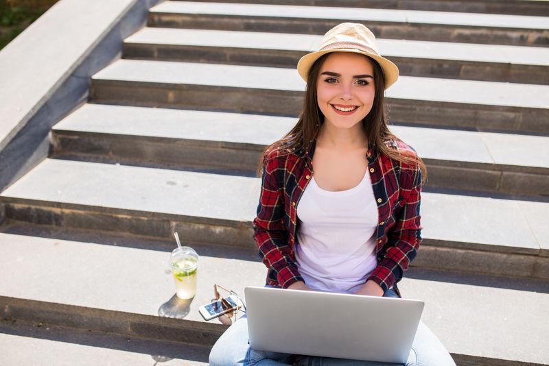 一个快乐的年轻女子坐在城市楼梯上,在室外使用笔记本电脑