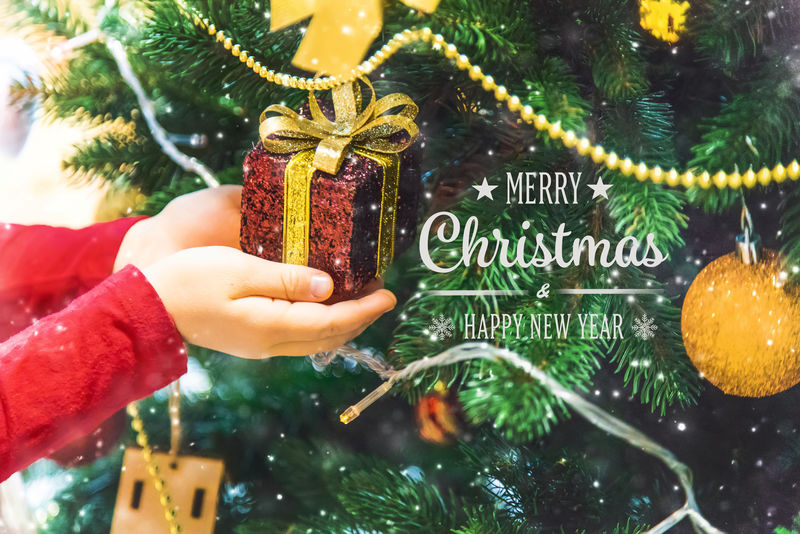 圣诞背景和手上有装饰品的孩子。新年。选择性聚焦。