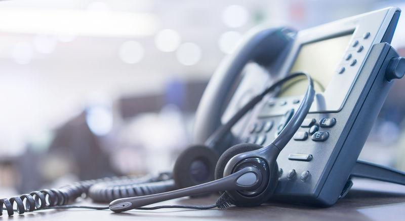 近距离软聚焦于具有复印空间背景的电话设备-位于操作室的办公桌上-用于客户服务支持(呼叫中心)概念