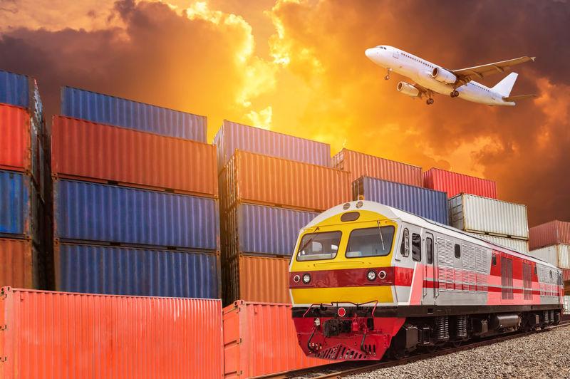 在日落时间上方的货运飞机上空-全球商业与货运货物列车和集装箱货物堆栈在码头上