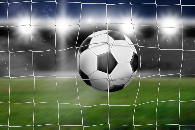 足球在球门内降落-在背景中可以看到体育场和泛光灯