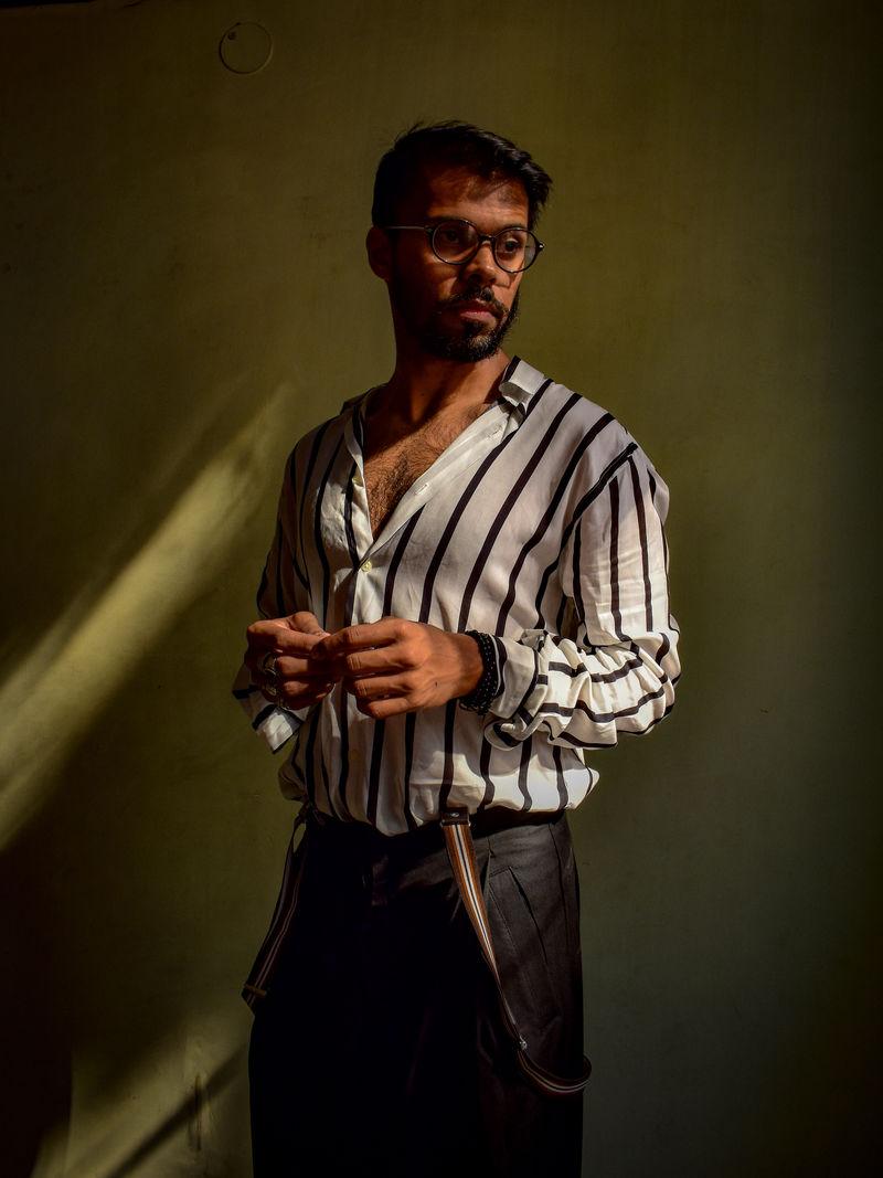 穿黑白条纹衬衫的男人站在灰色的W前面