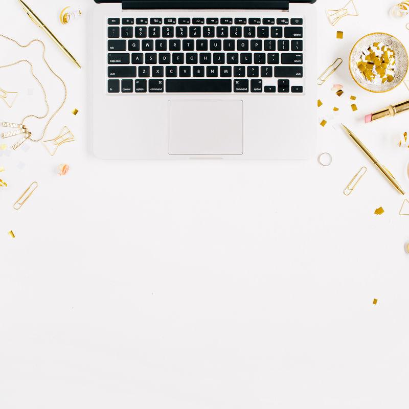 美容博客背景-工作区配有笔记本电脑、金色女性配件-白底金色金属箔、剪刀、钢笔、戒指、项链、手镯-平躺-顶视图办公桌