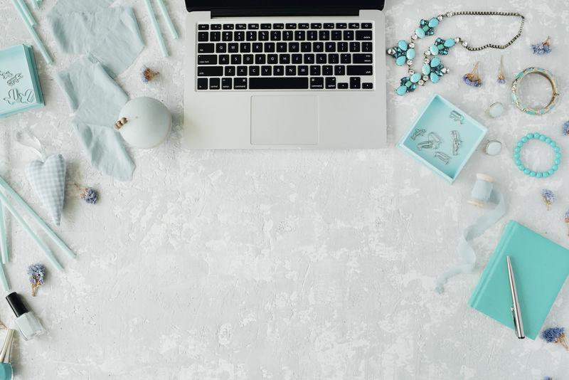 平躺-顶视图办公桌-Mint工作区配有笔记本电脑、日记、Mint装饰、配件和灰色混凝土背景的线轴