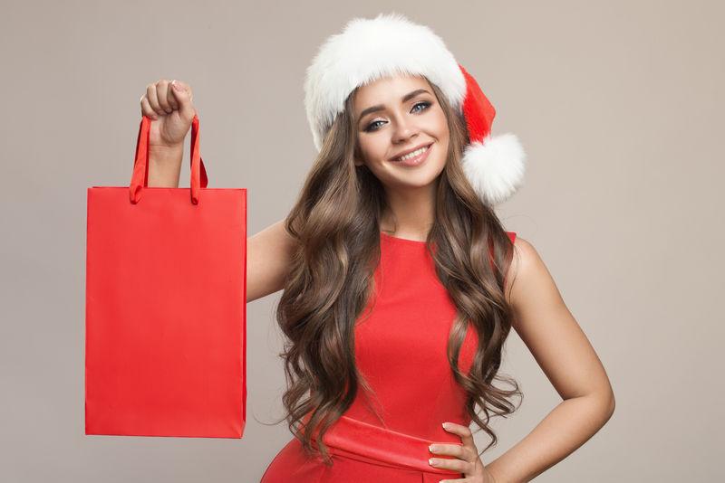 一个戴着圣诞帽-手里拿着购物袋的漂亮可爱的女人的画像-灰色背景