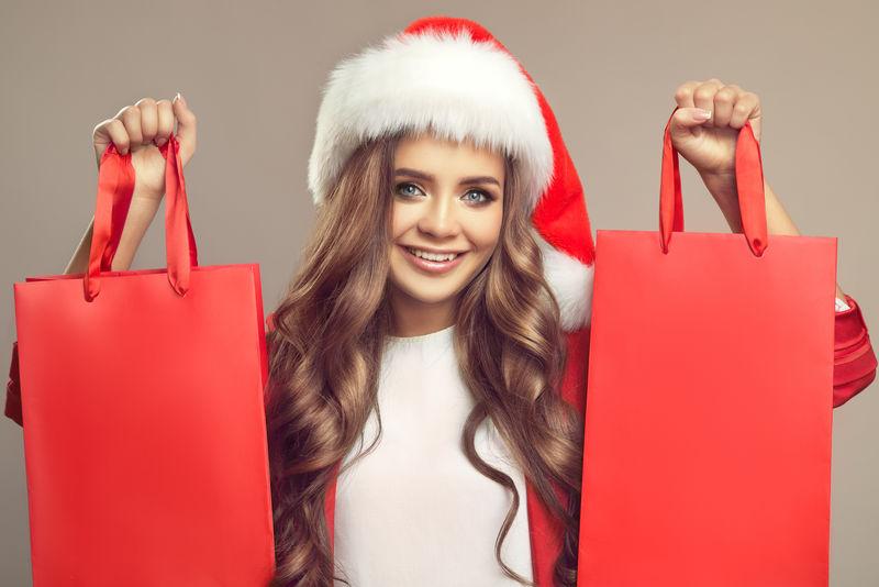 圣诞帽上可爱微笑的女人的肖像-手里拿着红色的购物袋-圣诞节
