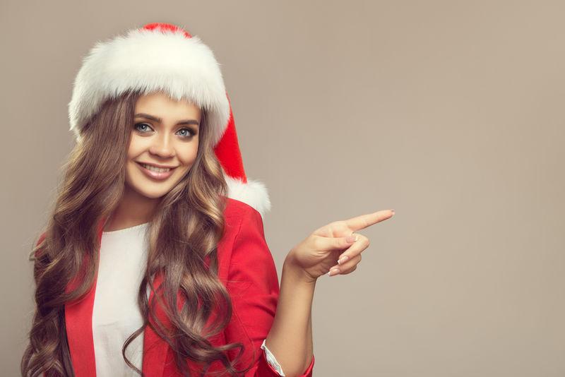 圣诞帽上可爱微笑的女人的肖像-用手指着复制空间-圣诞节