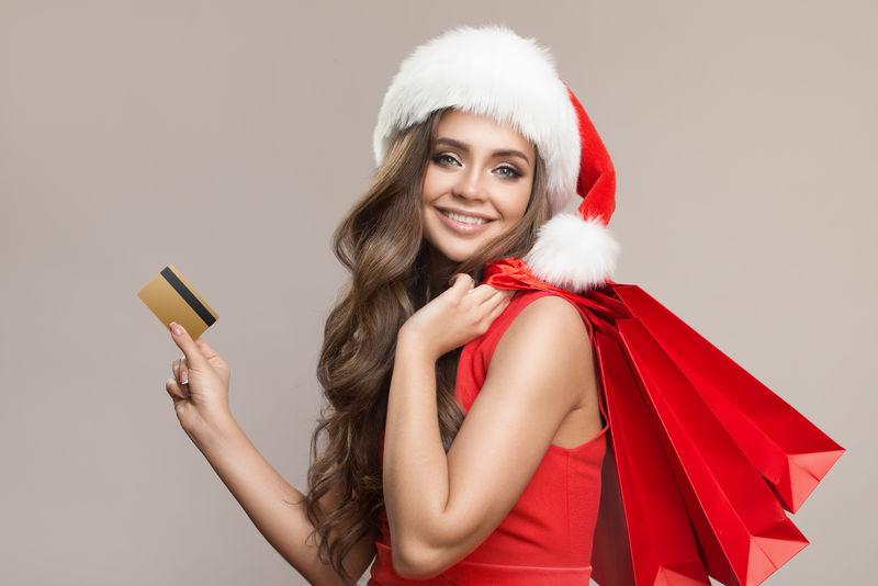 一个戴着圣诞帽-手里拿着购物袋和信用卡的可爱女人的肖像-灰色背景