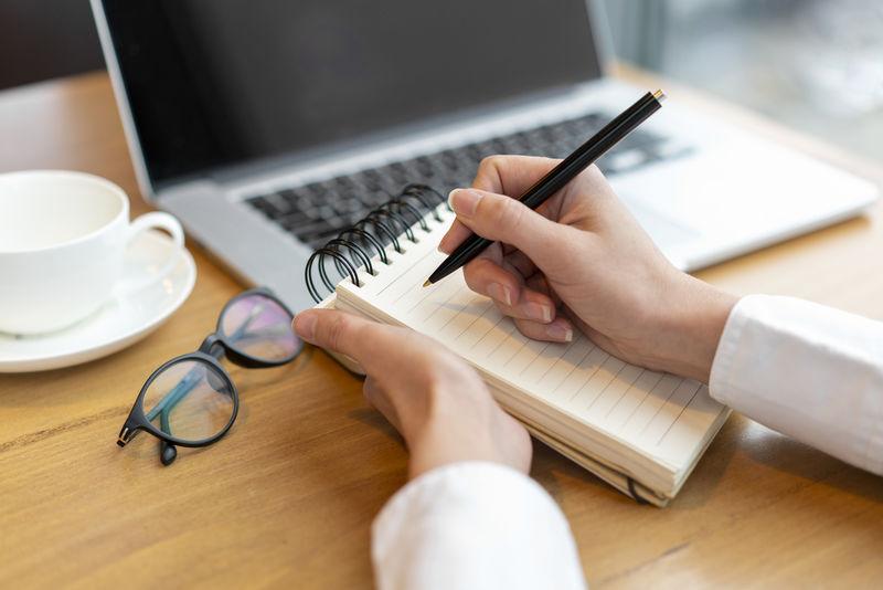在工作场所用钢笔和智能手机在笔记本上写字的商人