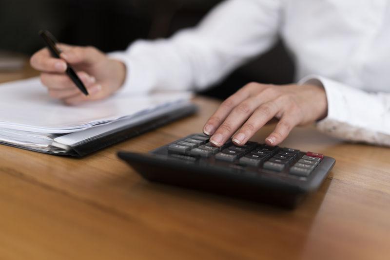 工作中的商人-坐在木桌旁操作笔记本电脑的人的特写俯视图