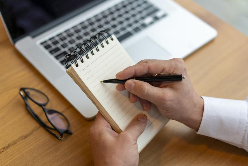 商业理念-女士用笔记本电脑记录项目并在办公桌上报告-背光、强光效果、特写、侧视图、复制空间