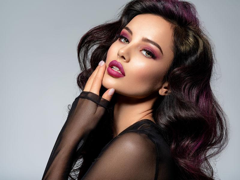 美丽明亮的化妆妇女-长黑色卷曲发型-勃艮第口红鞋面看起来灰色背景-特写调肖像