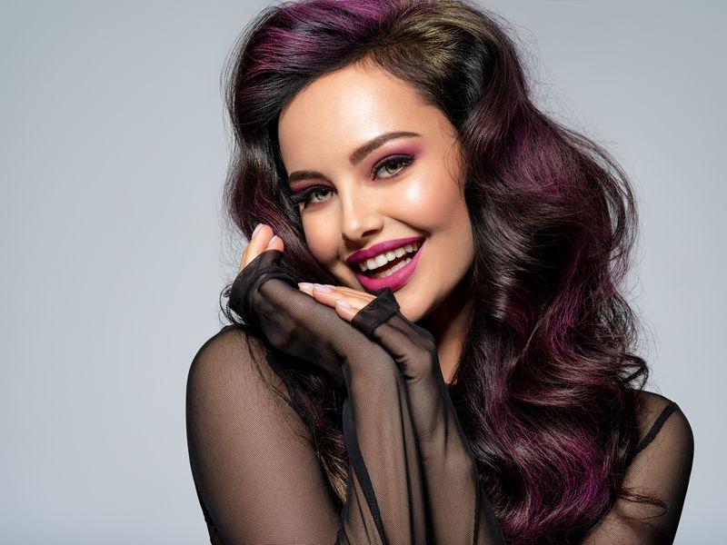 她脸上带着鲜艳的樱桃口红-长着黑色长发的快乐女孩-风趣的女孩看着镜头-美丽的年轻女子的肖像-带着明亮的栗色妆