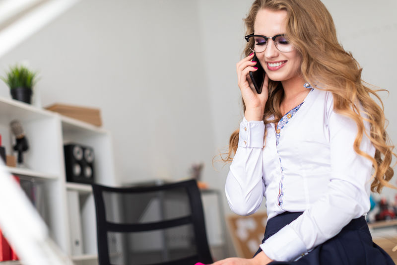 一个漂亮的年轻女孩坐在办公室的桌子上,正在打电话。在女孩面前有文件。