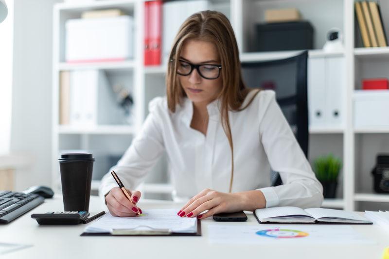 坐在桌子旁用电脑、文件和计算器工作的年轻女孩