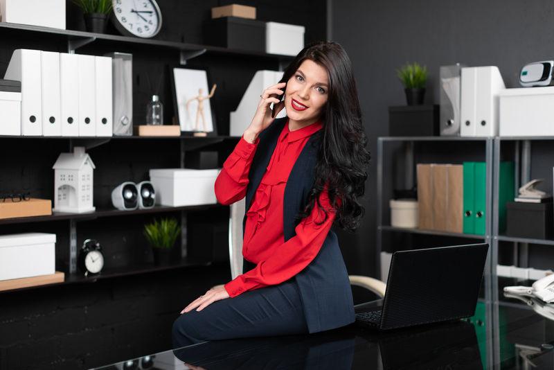 一位优雅的女士坐在桌上,办公室里放着笔记本电脑,一边打电话